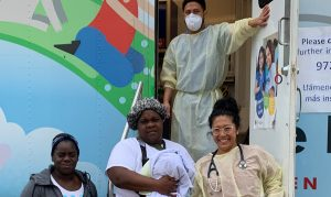 Family Nurse Practitioner Vicky and medical assistant Andres with clients outside The Doctor Spot